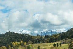 低云盘旋了在谷和积雪的喀尔巴阡山脉在罗马尼亚 免版税图库摄影