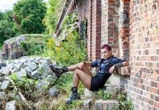 低劣的女孩坐一座老城堡的门廊 免版税库存照片