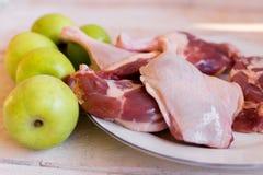 低头新鲜的肉,未加工的鸭子腿用木表面上的果子 免版税库存图片