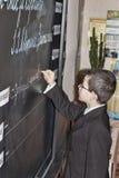 低年级的一个未知的学生在黑板的写一些 免版税库存照片