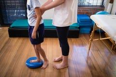 低拿着男孩的部分女性治疗师站立在蓝色重音球 免版税库存照片