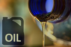 低油问题和摩托车从瓶特写镜头的脖子的机油流程液体小河  免版税库存图片