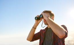 低角度使用双筒望远镜的射击了一个年轻人 库存照片