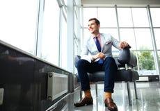低角度射击了在一个时髦的现代办公室空间的一个英俊的年轻商人与大窗口 免版税库存照片
