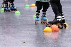 低角度射击了家庭,年轻母亲,并且孩子在四轮溜冰乘坐在公园 图库摄影