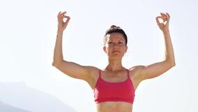 低角度弧做与山的被射击妇女放松的瑜伽在背景 影视素材