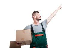 低角度拿着纸板箱的搬家工人人指向  库存照片