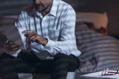 低角度观点的一个成熟男性坐一张床在屋子和h里 免版税图库摄影