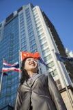 低角度观点的在一个大厦前面的女实业家与中国旗子在背景中 库存图片