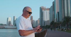低角度观点的在被弄脏的街道背景藏品智能手机的可爱的商人在使用4G互联网的手上 股票录像