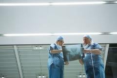 低角度观点的外科医生谈论X-射线在走廊 库存照片