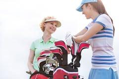 低角度观点的愉快的女性高尔夫球运动员谈话反对清楚的天空 免版税库存照片