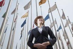 低角度观点的有旗子的微笑的年轻女实业家 免版税图库摄影