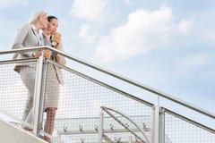 低角度观点的有看起来一次性的咖啡杯的年轻女实业家去,当支持栏杆反对天空时 库存照片