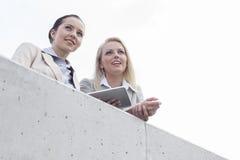 低角度观点的有看起来数字式的片剂的年轻女实业家去,当站立在大阳台反对天空时 库存图片