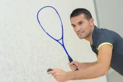 低角度视图确定了打网球的年轻人室内 免版税库存图片