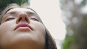 低角度面孔与闭合的眼睛思考的射击妇女感觉与自然团结 股票录像