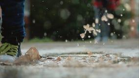 低角度,特写镜头,跑通过水坑在雨以后的夏日的无法认出的孩子 无忧无虑的孩子在水坑跑 影视素材