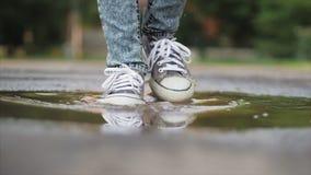 低角度,特写镜头,跑通过水坑在雨以后的夏日的无法认出的孩子 无忧无虑的孩子在水坑跑 股票录像
