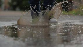 低角度,特写镜头,跑通过水坑在雨以后的夏日的无法认出的孩子 无忧无虑的孩子在水坑跑 股票视频