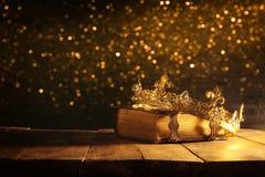 低调女王/王后/国王冠在旧书 被过滤的葡萄酒 幻想中世纪期间 库存图片