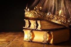 低调美丽的女王/王后/国王冠在旧书 被过滤的葡萄酒 幻想中世纪期间 图库摄影