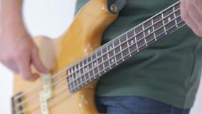 低音吉他在白色隔绝的串特写镜头的球员手指 影视素材