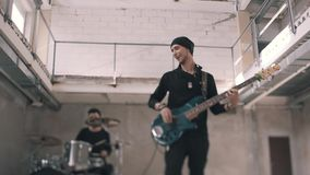 低音吉他弹奏者和鼓手戏剧在一间未完成的屋子 快乐的低音吉他弹奏者情感地执行他的部分 股票视频