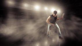 低音吉他球员行动狂放在阶段岩石 图库摄影