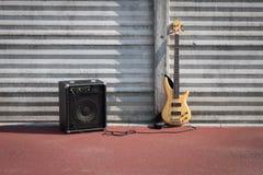 低音吉他和放大器对墙壁 免版税库存图片