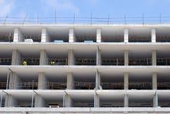 住宅公寓一个大建造场所与白具体地板和工作者的防护服装的 库存图片