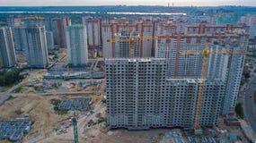 住宅区大厦建造场所鸟瞰图与起重机的在从上面日落,都市地平线 免版税库存照片