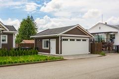 住宅房子独立式车库有柏油路的在前面 免版税库存照片