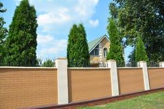 住宅砖篱芭 操刀与金钟柏树的砖 库存图片