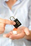 住家安全或保险的概念与暗号锁在一个微型房子的屋顶举行了 免版税库存照片