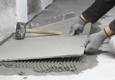 住所改善,整修-建筑工人铺磁砖工是tili 库存照片
