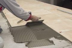 住所改善,整修-建筑工人铺磁砖工铺磁砖,陶瓷砖地板胶粘剂,有灰浆的修平刀 库存照片