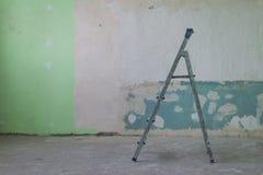 住所改善:在墙壁附近的肮脏的梯子 免版税库存照片
