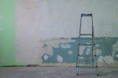住所改善:在墙壁附近的肮脏的梯子 库存图片