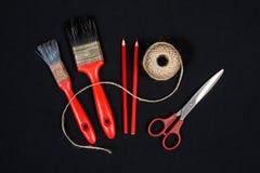 系住,两把红色刷子蜡笔和剪刀 免版税库存图片