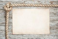 系住,纸片和木头背景 库存图片