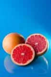 整体切了在蓝色背景的葡萄柚,垂直的射击 免版税图库摄影