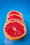 整体切了在蓝色背景的葡萄柚,垂直的射击 库存图片