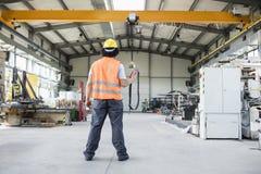 年轻体力工人运行的起重机全长背面图在工厂 免版税库存照片
