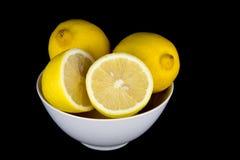 整体和被切的柠檬在白色碗在黑背景 库存照片