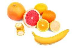 整体和裁减热带香蕉和水多,酸柠檬和成熟葡萄柚和明亮的桔子,隔绝在白色背景 图库摄影