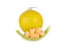 整体和部分切了与词根的新鲜的黄色瓜在白色后面 免版税库存图片