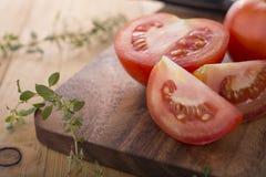 整体和部分切了新鲜的蕃茄用在切板的草本 免版税库存照片
