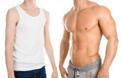 体型教练题目:美丽的强的爱好健美者教练在studi的白色背景隔绝的一个稀薄的人旁边站立 免版税图库摄影