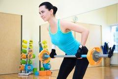 体型概念-行使与在健身房的杠铃的妇女 图库摄影